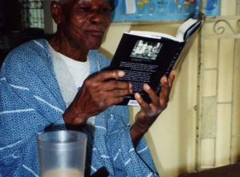 Mr. Bolarinwa, my father's friend, reading Gods of Noonday